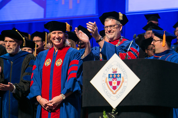 Honorary degree recipient Marty Wilke, a broadcast television executive and DePaul alumna, joins the Rev. Dennis H. Holtschneider, C.M., president of DePaul, as they applaud the graduates Sunday, June 11, 2017, during the DePaul University College of Computing and Digital Media and the College of Communication commencement ceremony at the Allstate Arena in Rosemont, IL. (DePaul University/Jamie Moncrief)