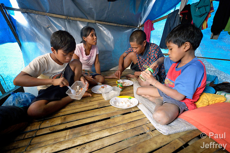 A family eats dinner in their shelter, part of a group of almost 200 residents of the indigenous village of San Fernando who fled their home on March 14, 2012, shortly after the March 5 assassination of Jimmy Liguyon, the baranguay captain. Mr. Liguyon was killed by a paramilitary squad led by Aldy Salusad, which was angered by Liguyon's refusal to sign papers ceding the community's land to a large mining company. Convinced they were also in danger from Salusad and his military allies, his widow and other community members fled to the provincial capital of Malaybalay, where they have set up temporary shelters on the grass in front of provincial offices. They promise not to leave until there is justice in the killing of Liguyon..