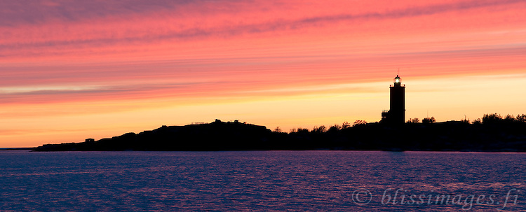 Russarö lighthouse stands sentinel between Hanko, Finland and the open sea,   is silhouetted against brilliant pastel sunset.