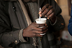 An African migrant takes hot milk sheltered from the cold under the arches of Irun City Council. Irun (Basque Country). Ocotber 28, 2018. A group of volunteers has created a host network to serve migrants and inform about the public services they are entitled to and the ways to cross the border. This group of volunteers is avoiding a serious humanitarian problem Irun, the Basque municipality on the border with Hendaye. As the number of migrants arriving on the coasts of southern Spain incresead, more and more migrants are heading north to the border city of Irun. French authorities have reacted by conducting random checks as far as the city of Bordeaux, more than 200 kilometers north of the border. Migrants who are caught are then deported back to Irun. (Gari Garaialde / Bostok Photo).