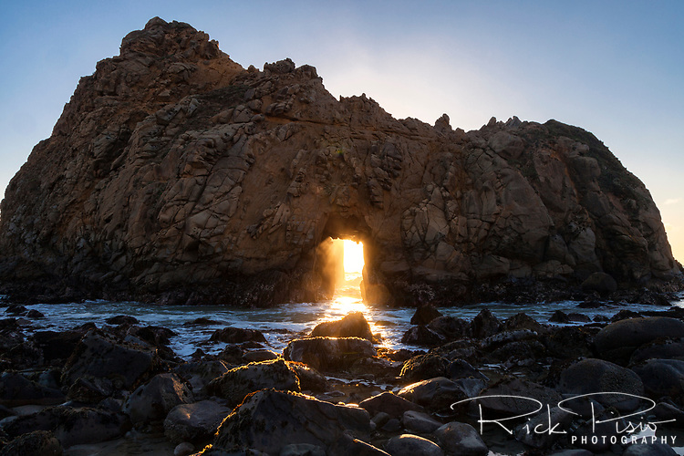 Sunlight and surf stream through Keyhole Arch at Pfeiffer Beach along California's Big Sur Coastline in the days preceeding and following the winter solstice.