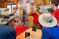 Photo story of Philmont Scout Ranch in Cimarron, New Mexico, taken during a Boy Scout Troop backpack trip in the summer of 2013. Photo is part of a comprehensive picture package which shows in-depth photography of a BSA Ventures crew on a trek.  In this photo BSA Venture Crew scouts learn how to properly reload shotgun shells . The shells being reloaded were used by the scout at the skeet shooting range in the backcountry at Philmont Scout Ranch.   <br /> <br /> The  Photo by travel photograph: PatrickschneiderPhoto.com