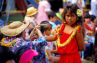 A kapuna, or elder, ties a ti-leaf around a local young girl's wrist during Lei Day festivities at Lili'oukalani School in Kaimuki.