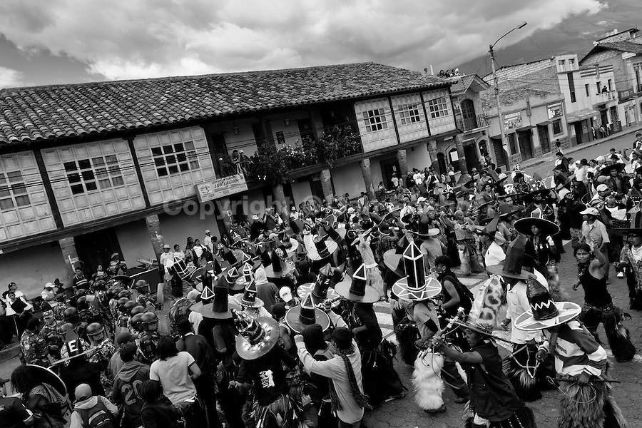 Indians, wearing cardboard hats, dance wildly during the Inti Raymi (San Juan) festivities in Cotacachi, Ecuador, 24 June 2010. 'La toma de la Plaza' (Taking of the square) is an ancient ritual kept by Andean indigenous communities. From the early morning of the feast day, various groups of San Juan dancers from remote mountain villages dance in a slow trot towards the main square of Cotacachi. Reaching the plaza, Indians start to dance around. They pound in synchronized dance rhythm, shout loudly, whistle and wave whips, showing the strength and aggression. Dancers from either the upper communities (El Topo) or the lower communities (La Calera), joined in respective coalitions, seek to conquer and dominate the square and do not let their rivals enter. If not moderated by the police in time, the high tension between groups always ends up in violent clashes.