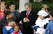 United States President George W. Bush holds a turkey egg given to him by one of the children after he pardoned Katie the turkey at the annual turkey pardoning ceremony in the Rose Garden of the White House in Washington, DC on 26 November, 2002.<br /> Credit: Ron Sachs / CNP
