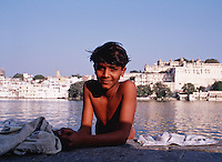 A smiling Indian boy before a bathing lake on the edge of the city. Udaipur, India.
