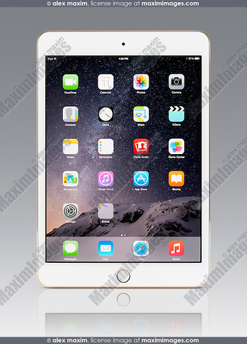White gold Apple iPad Mini 3 tablet computer with desktop icons on its display. Isolated with clipping path on gray background.