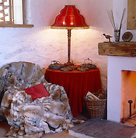 Next to the roaring fire, a warm and sensual corner of the living room with an inviting armchair covered in a fur throw