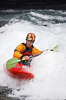 Andrew Jobe paddles a whitewater kayak through a wave on the Kananaskis River, Kananaskis County, Alberta, Canada
