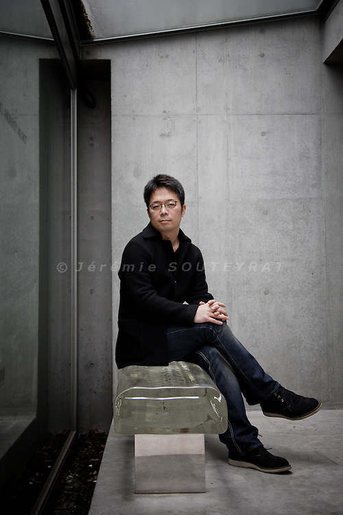 "Tokyo, November 26 2010 - Portrait of the designer Yoshioka Tokujin in his design studio and house in the Shibuya area. Yoshioka Tokujin seating on the "" water block "" bench that he created, in front of his house. The bench is made of optical glass."