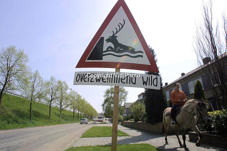 """Foto: VidiPhoto..LENT - Een voor Nederlandse begrippen onbekend waarschuwingsbord in het dorp Lent wordt door actievoerder Richard Pals nog eens goed vastgeschroefd. De inwoners van het Waaldorp protesteren op deze ludieke wijze tegen de plannen van het Rijk om de dijk bij Lent te verleggen. Gevolg is dat een deel van het dorp gesloopt moet worden. Volgens onderzoek van een ingenieursbureau zou het wild, zoals herten, bij Lent het makkelijkst de Waal over kunnen zwemmen. Vandaar het waarschuwingsbord """"Overzwemmend wild"""". Ook de gemeente Nijmegen is tegen. De Kamer debatteert nog voor de zomer over de dijkverlegging bij Lent."""