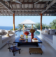 The open-air poolside living area has views over the swimming pool and gazebo to the ocean beyond