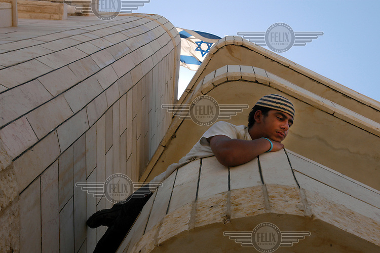 A young Israeli settler on the balcony of an abandoned Palestinian building in the Muwasi area. In advance of the Israeli disengagement from Gaza, right-wing settlers took over the building and declared it to be a new outpost, Tal Yam. The Israeli government disbanded the settlements in Gaza in August 2005.