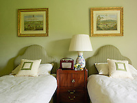 Twin single beds in the guest bedroom share a bedside table