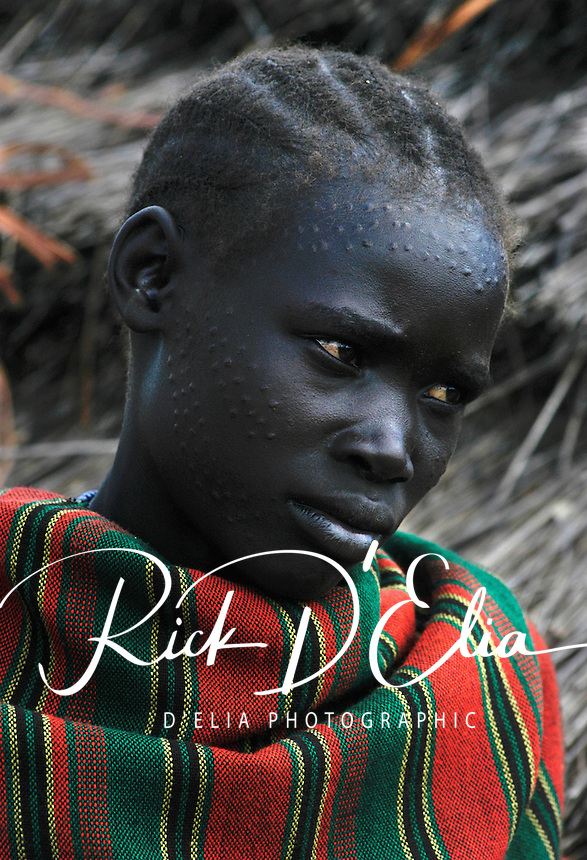 Kosho Madalena, 12, wears decorations in her skin which she says signifies that she is ready for marriage as an Ik girl (woman). October 22, 2003. The Ik people are a tiny tribe who lives on the edge of the Rift Valley in Northeastern Uganda near the town of Kaabong. (Rick D'Elia)<br />