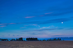 The nearly-full moon rises as the purple and blue colors of twilight fill the sky in Flathead County, Montana.