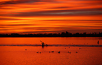 A kayaker moves through the water as the sun sets behind Mission Bay on a winter day in San Diego, California. Mission Bay Park, the largest man-made aquatic park in the country, consisting of 4,235 acres.