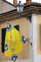 Flag of the Corso Contrada on flagpole in Asciano, inTuscany, Italy