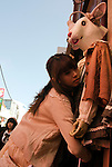 A woman changes the clothes on a mannequin in Harajuku shopping district.