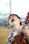 A young smiling boy plays his guitar or ukulele