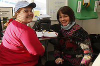 "February 16, 2013  Logistics volunteers Brittany Hanson (L) and Teri Paton work the dispatch room at the Willow airport in support of the Iditarod Air Force during day one of the ""Food Fly""  as musher food, straw, HEET and people food is flown to the 4 checkpoints on the east side the Alaska Range. ..Photo Copyright Jeff Schultz  -- Do not reproduce without written permission"