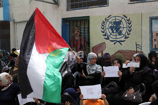 Palestinian women hold up their refugee ration cards during a protest demanding the United Nations Relief and Works Agency (UNRWA) to resume aid for refugees in Gaza City April 8, 2013. The main U.N. humanitarian agency for Palestinians closed all of its relief and distribution centres in Gaza after protesters stormed its headquarters on Thursday demanding it to reverse a decision to cut annual cash handouts of $40 to the poorest beneficiaries. Photo by Ashraf Amra