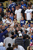 Fans battle for a foul ball during a game between the Milwaukee Brewers and the Los Angeles Dodgers at Dodger Stadium on May 31, 2012 in Los Angeles,California. Milwaukee defeated Los Angeles 6-2.(Larry Goren/Four Seam Images)