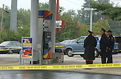 """Manassas, VA - October 10, 2002 --  Prince William County Police officesr look at the gas pump the morning after a Gaithersburg man was murdered while pumping gas at a Sunoco station.  It is still unclear if the man is another victim of the """"Beltway Sniper"""".  <br /> Credit: Ron Sachs / CNP<br /> (RESTRICTION: NO New York or New Jersey Newspapers or newspapers within a 75 mile radius of New York City)"""