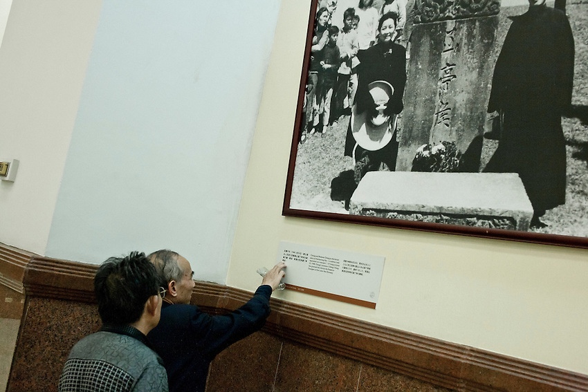 Des touristes chinois du continent lisent avec difficulté les explications sous une photographie montrant Chang Kai Shek et son épouse devant la tombe des ancêtres de la famille Soong.