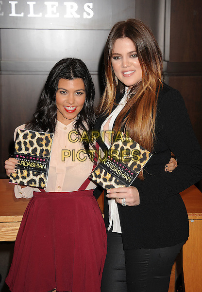 "Kourtney Kardashian, Khloe Kardashian Odom .at the ""Dollhouse"" book signing at Barnes & Noble bookstore at The Grove in Los Angeles, California, USA, November 18th, 2011.  .half length siblings sisters houndstooth patterned tights black  red pink skirt braces shirt white blouse jacket jeans .CAP/ROT/TM.©TM/Roth Stock/Capital Pictures"