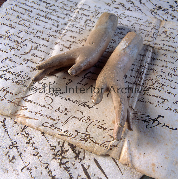 A pair of sculpted plaster hands rest on parchment covered in handwriting.