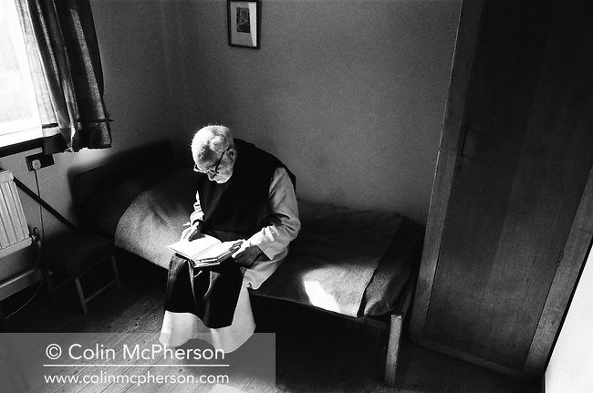 A monk reading in his room at Sancta Maria Abbey at Nunraw, East Lothian, home since 1946 to the Order of Cistercians of the Strict Observance. Around 15 monks were resident at Nunraw in 1996, undertaking a mixture of daily tasks and strict religious observance. The present purpose-built building dates from 1969 when the monks moved from the nearby Nunraw house.