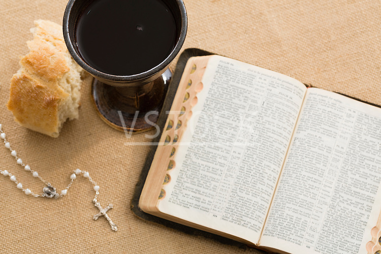 High angle view of open Holy Bible, pearl rosary beads, piece of bread and chalice with wine