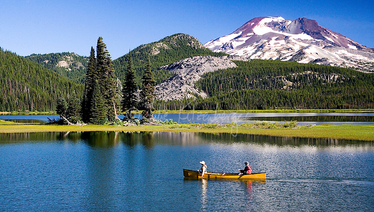 Fine art landscape of canoers wearing white and red jackets, guiding a yellow canoe across Sparks Lake, with green island strip supporting a few tall pine trees in the middle of the lake, and an edge of pine trees, hills, and Mount Bachelor in the background, Central Oregon, U.S.A.