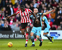 Lincoln City's John Akinde shields the ball from Stevenage's Scott Cuthbert<br /> <br /> Photographer Andrew Vaughan/CameraSport<br /> <br /> The EFL Sky Bet League Two - Lincoln City v Stevenage - Saturday 16th February 2019 - Sincil Bank - Lincoln<br /> <br /> World Copyright © 2019 CameraSport. All rights reserved. 43 Linden Ave. Countesthorpe. Leicester. England. LE8 5PG - Tel: +44 (0) 116 277 4147 - admin@camerasport.com - www.camerasport.com