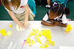 Anastasia Opshal pushes on a cookie cutter letter, as classmate Sheyan Johnson watches in their kindergarten class at Kennesaw Charter School in Kennesaw, Georgia, April 1, 2010. The school, which used to be managed by Imagine Schools, is now self-managed.