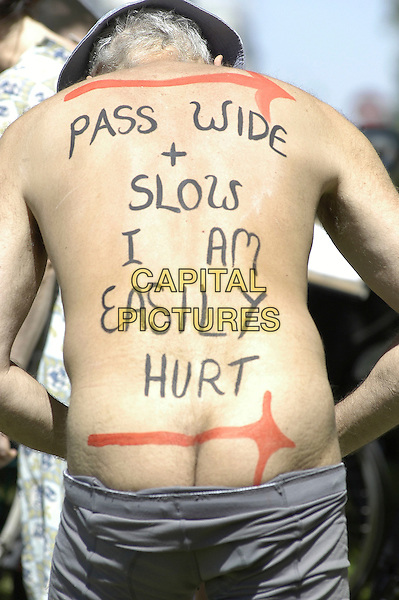 PARTICIPANT.People Taking part in the 3rd World Naked Bike Ride (& Skate) Protest Against Oil Dependency, starting and finishing at Wellington Arch, Hyde Park, London, 10th June 2006..half length nude bicycle nudist bare skin body paint painted slogan bum rear behind back.Ref: IA.www.capitalpictures.com.sales@capitalpictures.com.©Ian Allis/Capital Pictures