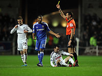 Pictured: Florent Malouda of Chelsea (2nd L) is shown a yellow card by match referee A Marriner (R), for his foul against Leon Britton of Swansea who is on the ground. Tuesday, 31 January 2012<br />