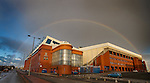 A rainbow embraces Ibrox Stadium and touches the ground at stairway 13 before fading away.
