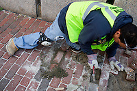 Pablo Mendez repairs a brick sidewalk for the Boston Public Works Department in Boston, Massachusetts, USA, on April 12, 2012.  The city uses a computer system to track public complaints and record work done by city crews to mitigate these complaints.  A supervisor or inspector photographs before and after pictures of the work in addition to making notes about the work done.