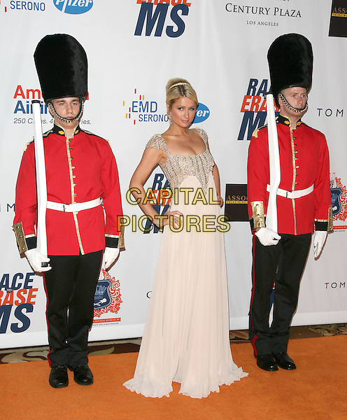 PARIS HILTON.The 18th Annual Race To Erase MS Gala held at The Hyatt Regency Century Plaza Hotel in Century City, California, USA. .April 29th, 2011.full length silver gold beads beaded embellished jewel encrusted hair up bun braid plait dress cleavage hands on hips beige maxi british guard uniform red guards soldier trousers jacket.CAP/RKE/DVS.©DVS/RockinExposures/Capital Pictures.