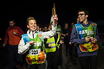 "A girl carries the baton as people run on the 20th Korrika. Castejon. (Basque Country). March 31, 2017. The ""Korrika"" is a relay course, with a wooden baton that passes from hand to hand without interruption, organised every two years in a bid to promote the basque language. The Korrika runs over 11 days and 10 nights, crossing many Basque villages and cities. This year was the 20th edition and run more than 2500 Kilometres. Some people consider it an honour to carry the baton with the symbol of the Basques, ""buying"" kilometres to support Basque language teaching. (Gari Garaialde / Bostok Photo)"