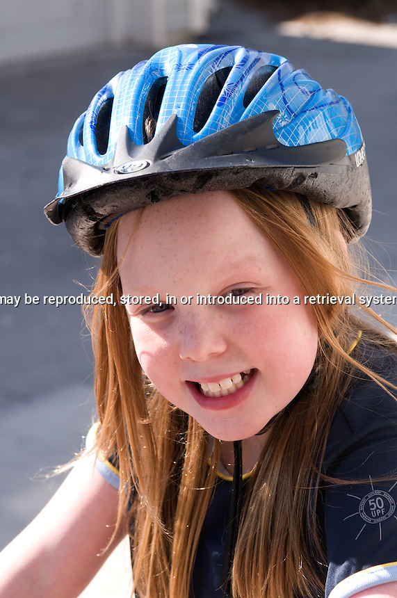 Young girl wearing a bike helmet and spf shirt