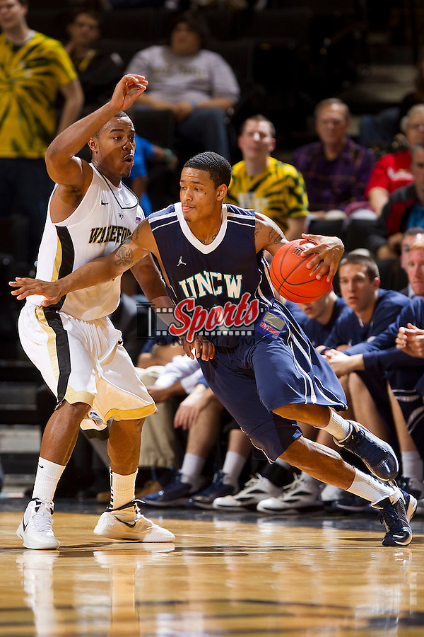 Donte Morales #1 of the UNC-Wilmington Seahawks dribbles around Tony Chennault #1 of the Wake Forest Demon Deacons during second half action at the LJVM Coliseum on December 21, 2011 in Winston-Salem, North Carolina.  The Demon Deacons defeated the Seahawks 87-78.  (Brian Westerholt / Sports On Film)