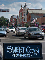 Sign advertising sweet corn for sale at Uptown Farmers market in Westerville, Ohio. Traffic on State Street in background with town center.