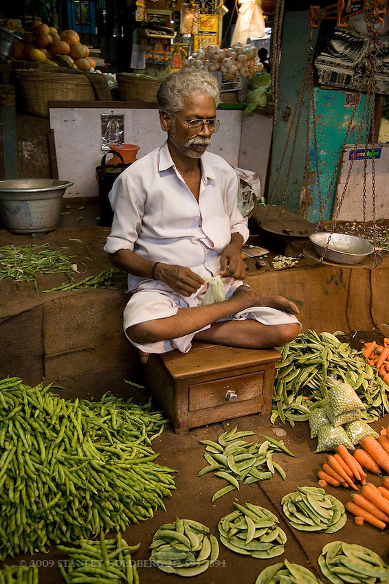 Indian Farmer sells peas and carrots in open air market southern India
