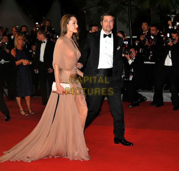 "ANGELINA JOLIE & BRAD PITT .Leaving the premiere of ""Inglorious Basterds""  at the Grand Theatre Lumiere  during the 62nd Cannes International Film Festival, Cannes, France, .May 20th 2009..full length departures black suit tux tuxedo Tom Ford long beige peach silk dress maxi draped v-neck clutch bag satin shoes open toe cream couple leaving walking bow tie white shirt leg thigh slit split side profile sheer .CAP/PL.©Phil Loftus/Capital Pictures"