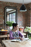 Kally Ellis, founder of McQueens Florist, in her kitchen surrounded by her flower arrangements