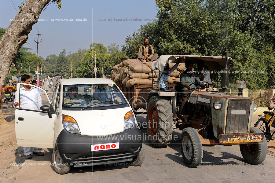 INDIA Banda U.P. , mini car Nano of indian Car maker TATA and tractor / INDIEN Banda , Kleinwagen Nano des indischen Autobauer TATA und Traktor auf Strasse