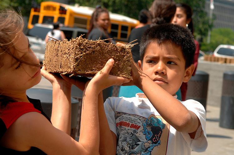 Ellezer Morales Lopez, 7, passes a brick made of mud and hay to Kalin Steen, 7, for an outdoor sculpture near the National Museum of the American Indian, by artist Nora Naranjo-Morse.